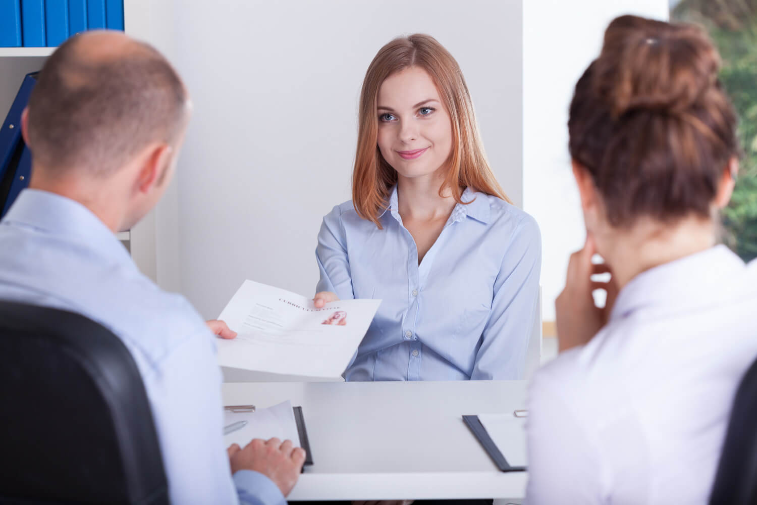 Woman at a job interview handing over CV/references