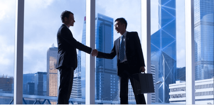 Two businessmen shaking hands in window